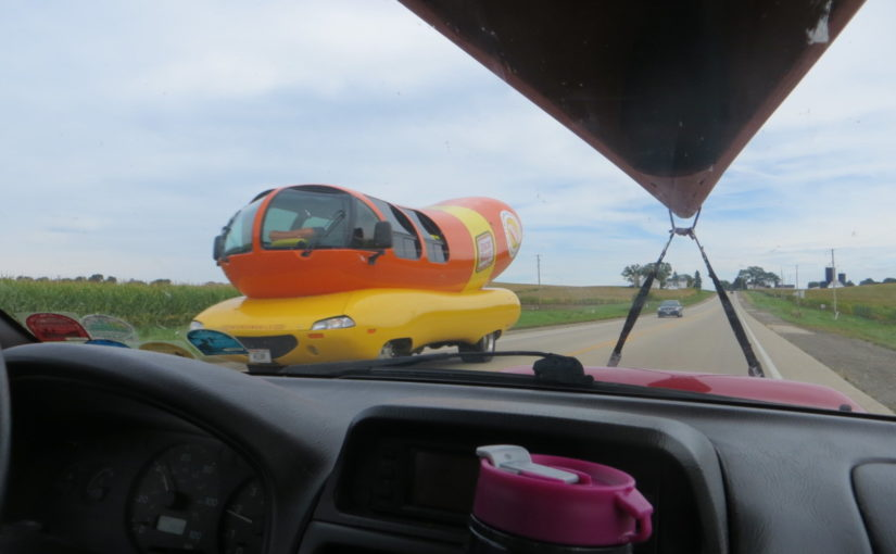 Wiener mobile from the view of a car with a canoe on top