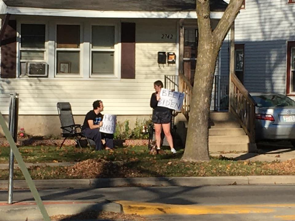 Neighbors holding signs Honk for Harris, Beep for Biden